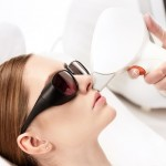 young woman receiving laser hair removal epilation on face isolated on white. laser skin care concept